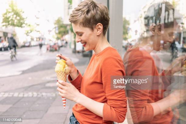 woman eating ice cream in front of shop, cologne, nordrhein-westfalen, germany - manches longues photos et images de collection