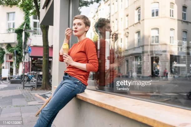 woman eating ice cream in front of shop, cologne, nordrhein-westfalen, germany - eis essen stock-fotos und bilder