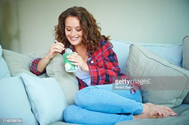 woman eating ice-cream on sofa - abbracciarsi a letto foto e immagini stock