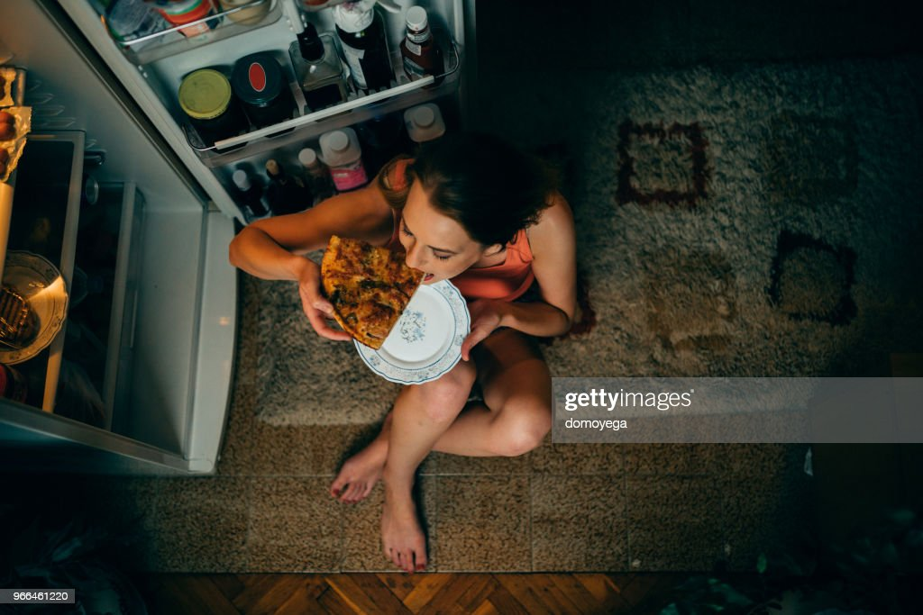 Woman eating in front of the refrigerator in the kitchen late night : Stock Photo