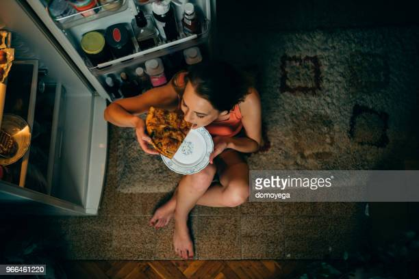 woman eating in front of the refrigerator in the kitchen late night - unhealthy living stock pictures, royalty-free photos & images
