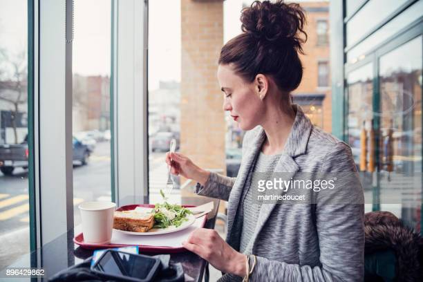 Woman eating lunch in a city cafe in winter.