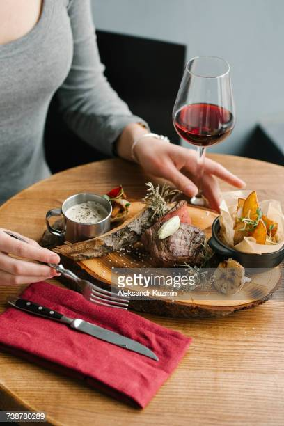 Woman eating meat with red wine