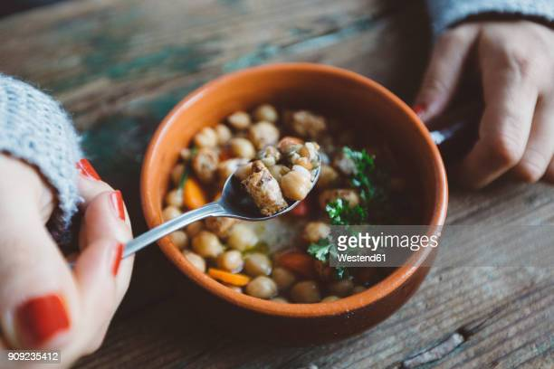Woman eating Mediterranean soup, close-up