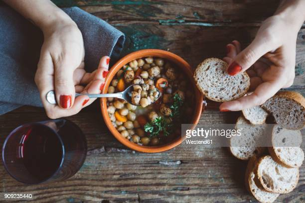 woman eating mediterranean soup with bread, close-up - glas serviesgoed stockfoto's en -beelden