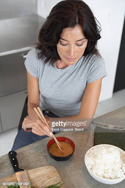woman eating miso soup in kitchen, elevated view - heidi coppock beard fotografías e imágenes de stock