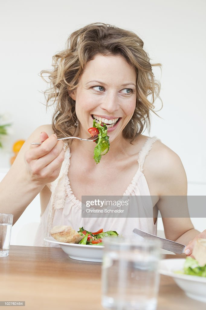 Woman eating mixed salad on table : Stock Photo