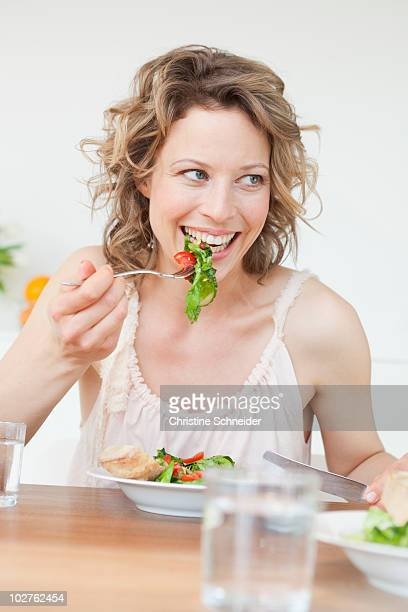 Woman eating mixed salad on table