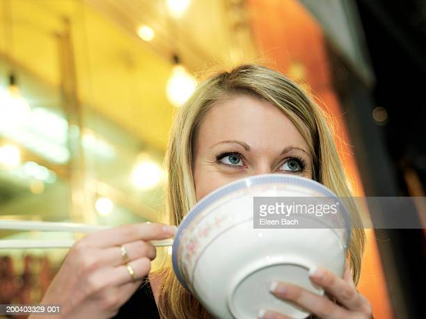 Woman eating noodles, bowl obscuring mouth, low angle view