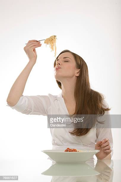 Young woman eating noodles, eyes closed