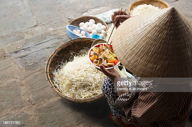 Woman eating noodles with baskets of produce