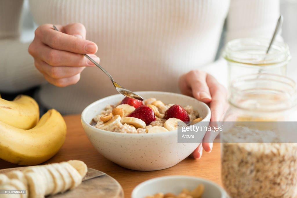 Vrouw die havermoutpap eet : Stockfoto