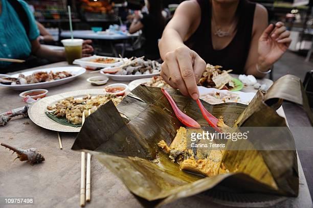 woman eating otah with plastic spoon in Penang