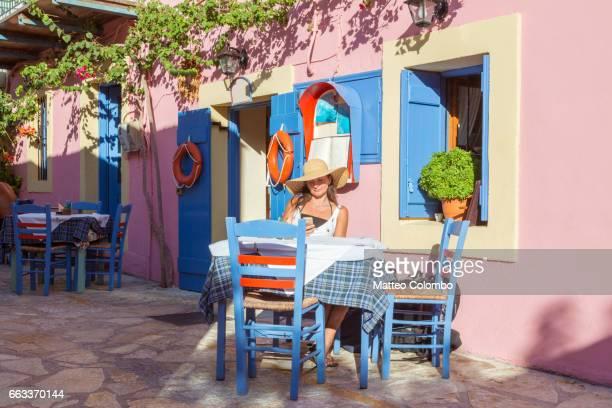 Woman eating out in a small greek village in summer. Kefalonia, Greek Islands, Greece (MODEL RELEASED)
