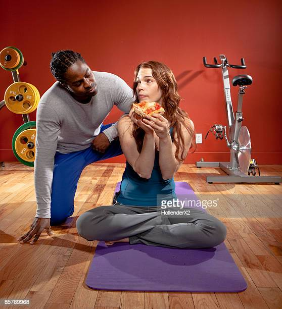 woman eating pizza at gym with man looking on