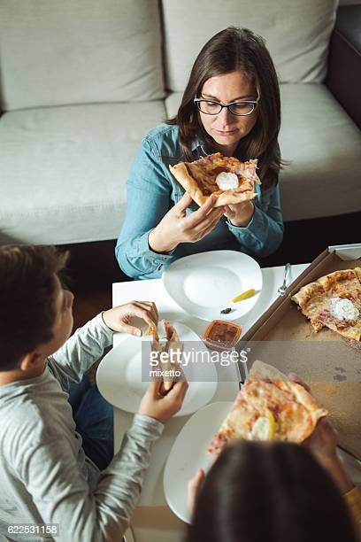 Woman eating pizza with family