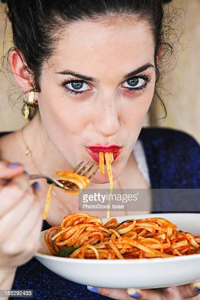 Woman eating plate of pasta