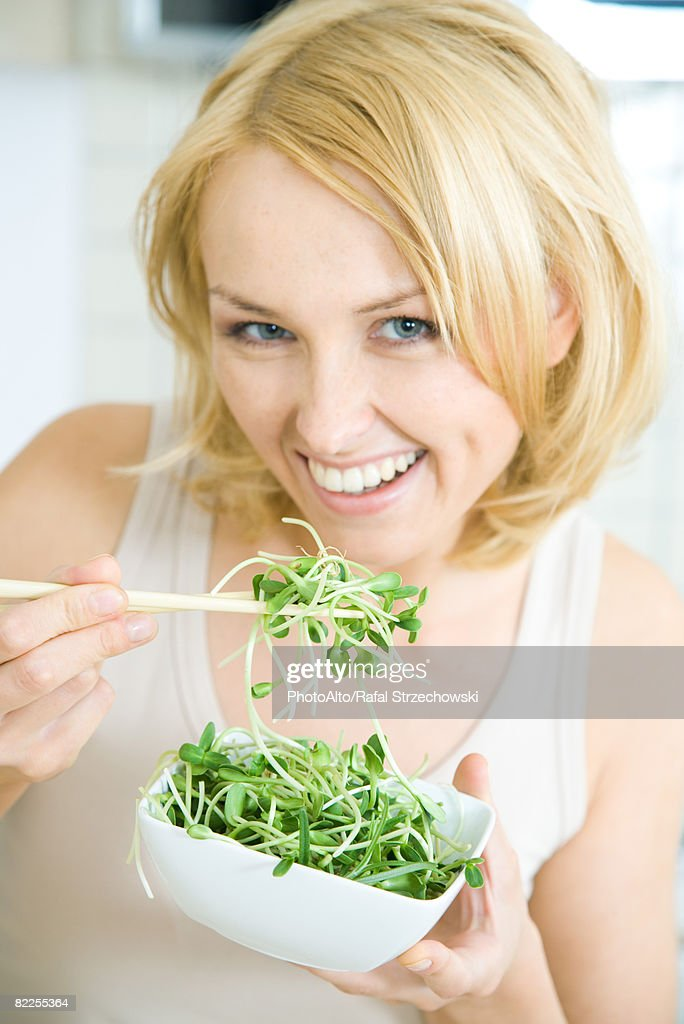 Woman eating radish sprouts with chopsticks, smiling at camera : Stock Photo