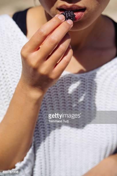 Woman eating ripe mulberries