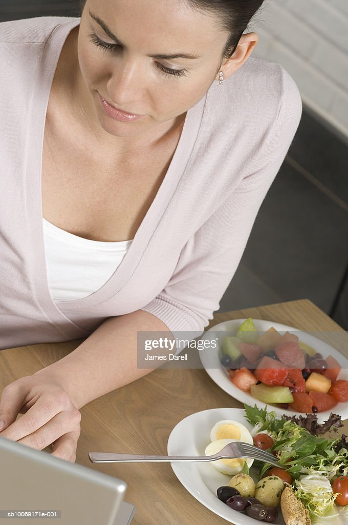 Woman eating salad and using laptop : Stockfoto