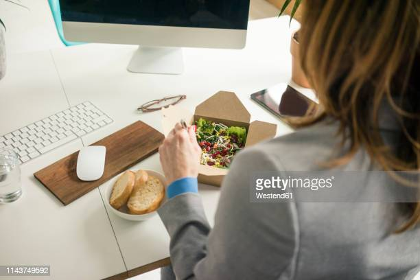 woman eating salad for lunch at her desk - 昼食 ストックフォトと画像