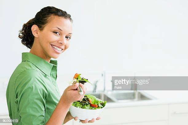 Woman eating salad in kitchen