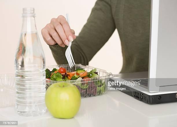 Woman eating salad next to laptop