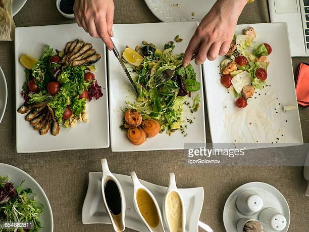 Woman eating salads in restaurant