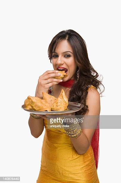 woman eating samosa the traditional indian snack - samosa stock photos and pictures