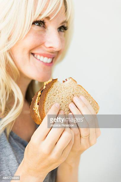 Woman eating sandwich with peanut butter