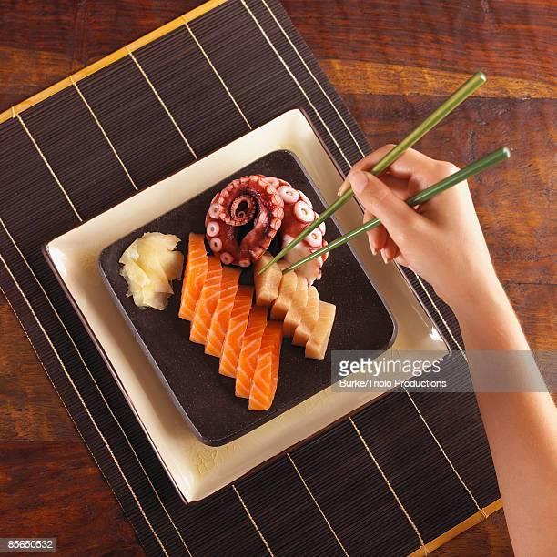 Woman eating sashimi with chopsticks