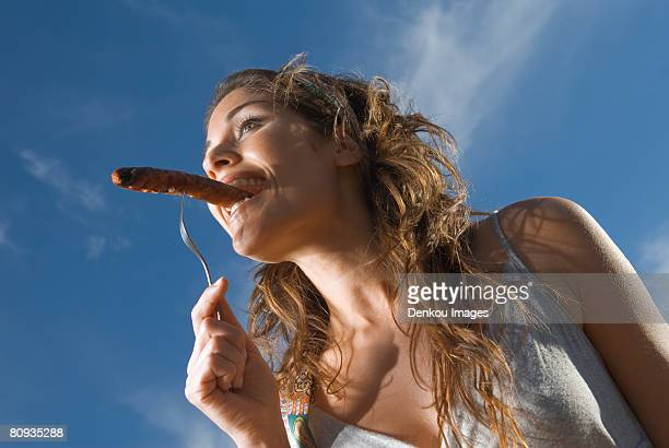 Woman eating sausage