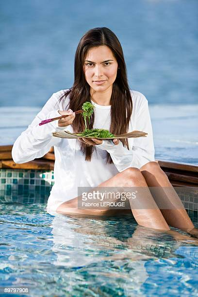 Woman eating seaweed with chopsticks
