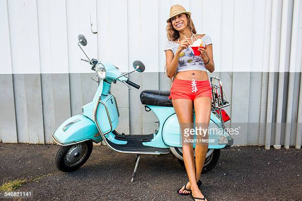 Woman eating shave ice near scooter