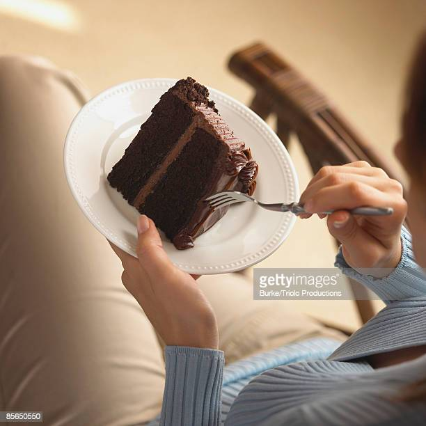 Woman eating slice of chocolate cake