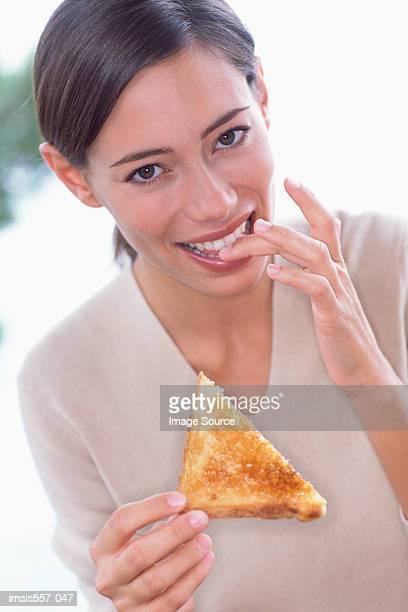 Woman eating slice of toast