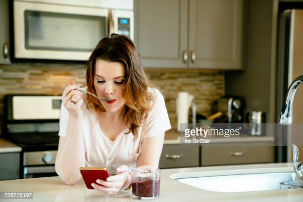 Woman eating smoothie and texting on cell phone