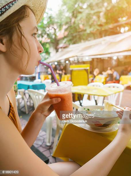 Woman eating soup and drinking juice