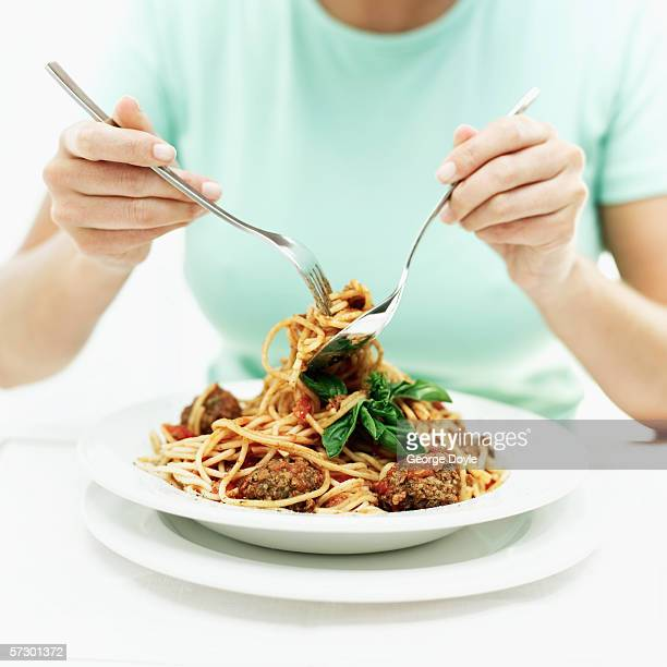 Woman eating spaghetti and meatballs with a fork and spoon