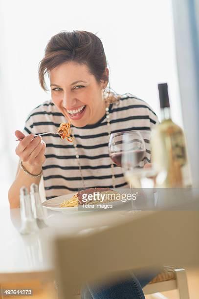 Woman eating spaghetti, Jersey City, New Jersey, USA