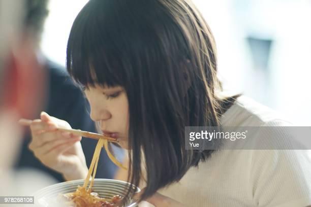 居酒屋で箸でスパゲティを食べる女性 - 食事 ストックフォトと画像