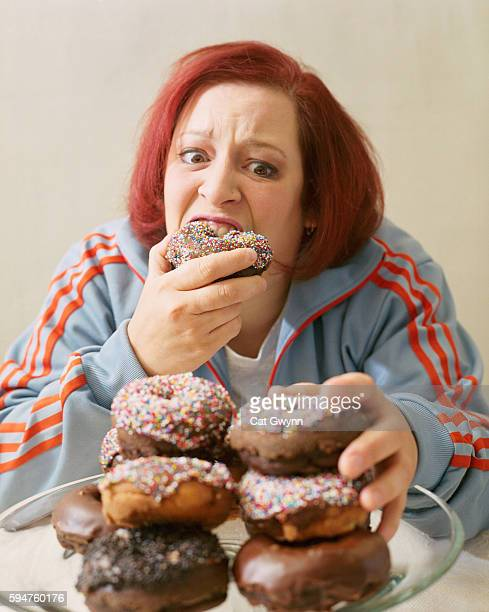 woman eating stacks of donuts - fat people eating donuts stock pictures, royalty-free photos & images