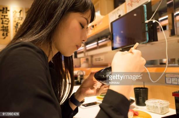 A woman eating sushi at a sushi bar.