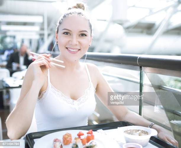 Woman eating sushi on the food court
