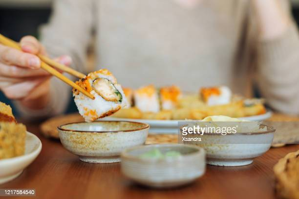 woman eating sushi rolls - wasabi stock pictures, royalty-free photos & images