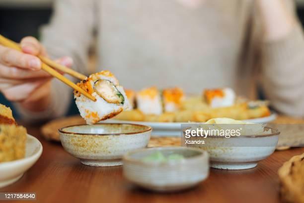 寿司ロールを食べる女性 - ワサビ ストックフォトと画像