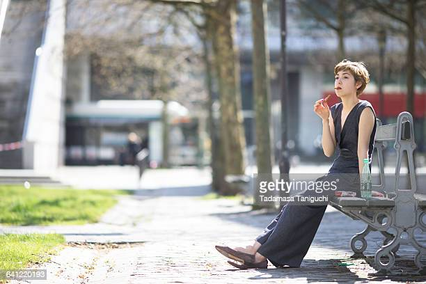 woman eating sweet at the park - ベンチ ストックフォトと画像