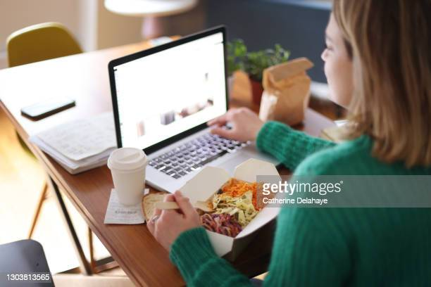 woman eating takeaway food while working on her laptop - mid adult stock pictures, royalty-free photos & images