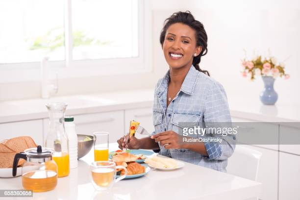 Woman eating tasty breakfast in the morning.