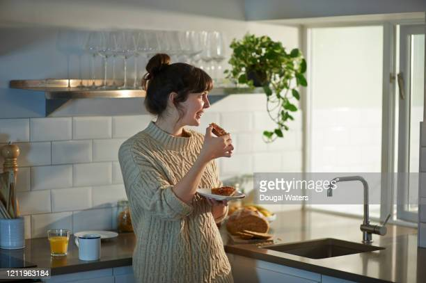 woman eating toast at breakfast and looking out of kitchen window. - snack stock pictures, royalty-free photos & images